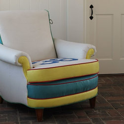 """Pieces in a Chatham Home - """"Sail Away"""" This French rollback chair was completely dismantled in our Chatham studio and then re-stuffed. It was then reupholstered by hand using jib sheets and spinnakers. Unexpected details include the tack points of a spinnaker used as accents on the sides and a two-sided seat cushion that can go  from a bold racing number (shown) to a more subdued solid white."""