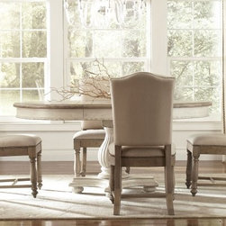 Riverside Coventry Round Dining Table - With a beautiful two-tone finish and traditional country style the Riverside Coventry Round Dining Table has a quiet elegance that will enhance any dining room. Built from hackberry and birch hardwood solids with ash veneers this table has a weathered driftwood finish on the top and a Dover white finish on the base. The included extension leaf lets you easily add extra room for guests and base levelers ensure perfect positioning of your table. About Riverside FurnitureRiverside has been growing for more than half a century. The company's founder Herman Udouj opened the doors to his first factory in 1946 and along with 12 employees he began making handcrafted furniture for the post-World War II Baby Boom era. Since then generations of customers have furnished their homes and offices with Riverside's wide range of furniture products. Riverside strives to be trusted for quality products that are an affordable value. It's just that simple. Notes on Riverside ConstructionAll Riverside domestic furniture is constructed of fine oak ash poplar and pine wood. These wood types are durable and feature beautiful open grains that make them much preferred among furniture manufacturers. Each piece of wood is first graded for quality then kiln-dried to remove excess moisture and prevent splitting. The wood is then constructed into a high-quality furniture piece using a combination of hardwood solids and hand-selected veneers. Techniques used on Riverside pieces include dovetail joinery heavy-duty drawer roller guides and multi-step finish applications that include hand-sanding and polishing for a deep lustrous result. All Riverside furniture is given this high-quality treatment to ensure the beauty and durability of your final product.