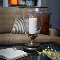 Antique Brass Hurricane - A classic accent for the coastal home and the inland deck, the hurricane lantern takes a stylish spin on an accent-lighting tradition in this Antique Brass Hurricane.� A smoothly-tapered cup resting in a dark antiqued brass base, turned to resemble the shape of an antique taper holder, makes the most of its space with a widely-flared lip in the same stylish, inviting designer metal.