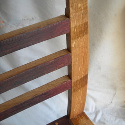"Wine Barrel Chair - Close-up showing seat back and finish detail. Note the contrasting color of natural white oak with the purple/burgundy stain achieved by ""toasting"" the inside of the barrel before wine is aged in it. Darker marks on the light-colored wood indicate where the hoop went around the outside of the barrel stave."
