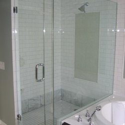 """Framless Return Shower Doors with Knee Walls - Shower enclosure has the door hinged off of left side. The panels are met at a 90 degree and are bonded together. Glass to glass bonding can only be installed in certain applications but offers a clean, low hardware look. Glass is ½"""" thick with chrome hardware."""