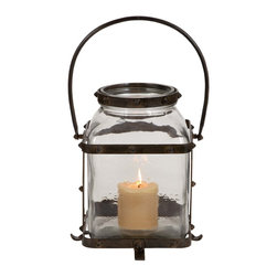 Metal Glass Lantern in Worn and Aged Finish - Elegant and attractive, this Metal & Glass Rustic Lantern features a rectangular glass case with a small, yet wide neck that is perfect for placing a lighted candle inside. The glass used is high quality and is protected on the outside by a durable metal frame. The clear glass ensures maximum light transmission and spreads warmth and light in your room. The sturdy frame sports a worn and tarnished look that recreates a rustic antique appeal that is more pleasant and cozy than harsh electrical lighting. A durable metal handle at the top allows you to carry this lantern around. With its worn and tarnished look, and exquisite old world design it seems to come straight out of an old western or classic movie. The only alternative to flaming torches in olden times, lanterns were the choice among light sources when on journeys or at home. It comes with following dimensions: