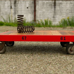 Custom Coffee Table Cart - This coffee table is made from an old industrial metal storage rack and wood reclaimed from an out of use conveyor belt.  The old casters are salvaged from a rusted out dumpster.