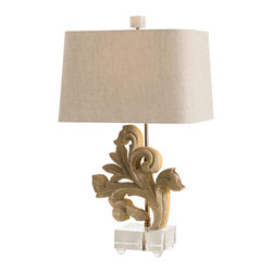 Picardi Hand Carved Solid Wood Fragment / Acrylic Lamp - An elegant botanical motif. Hand carved details in solid wood. The touch of a master craftsman. All give the Picardi Hand Carved Solid Wood Fragment/Acrylic Lamp the look of an unexpected treasure found at a European emporium. The pristine acrylic base lends a floating quality to the lamp base, which is topped with a warm Natural Linen Shade with Smoke Gray Cotton Lining.