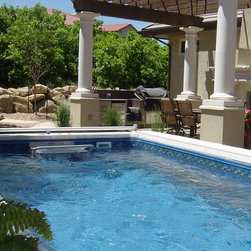 Original Endless Pools® - Bring a little old-world decadence into your backyard with a luxurious (and smartly efficient) Endless Pool. The contrasting textures of the dramatic columns against taupe stucco and the rugged stone wall set this installation apart.