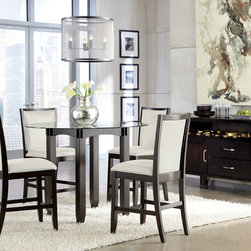 """Ashley Trishelle Dining Room Collection - With a sleek straight-line contemporary design bathed in a dark espresso color finish complementing the Okoume and Ash veneers, the """"Trishelle"""" Dining Collection features a sleek saber leg table with inset black glass in the table top along with upholstered chairs that create a stunning furniture collection."""