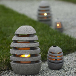 Stone Egg Candle Lanterns - VivaTerra - These lanterns have a natural yet very contemporary look to them. I love the idea of taking this medium and creating slats like a wooden piece where light can filter out for a great effect.