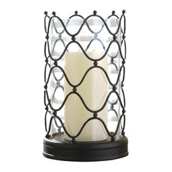 Arabesque Hurricane - Candlelight's glimmer takes on an adventurous air when it shines through this clear glass column in its shell of curving metal. Swaying lines and dark, dimensional metal beads join into an openwork screen that neatly encases the large glass cup, a curvaceous rippling latticework with a sensual feel. A thick turned base in the same deep brown metal provides a substantive visual pedestal to this tabletop candle lantern's form.