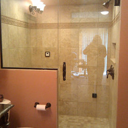 """Framless Return Shower Doors with Knee Walls - 1/2"""" Frameless door with kneewall panel and oil rubbed bronze hardware. Custom fabricated to fit arched opening."""