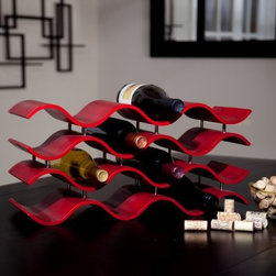 """Oenophilia Bali 12-Bottle Wine Rack - The Oenophilia Bali 12-Bottle Wine Rack features a design inspired by contemporary Indonesian furniture. This wooden wine rack is available in your choice of crimson red or ebony finish. The crimson finish has a deep red hue that complements any decor. The ebony finish is a deep rich blackish-brown hue and has a bit of a mahogany tint in certain light. Its graceful waves create compartments for 12 bottles of wine. Add that special splash of style to your kitchen or dining decor with this unique wine rack. Fully assembled. About OenophiliaWith a name Greek in origin meaning """"""""the love of wine """""""" Oenophilia delights in fulfilling its mission to bring together products that allow others to love wine with the passion that Oenophilia does. After creating their first product in 1983 the Oenophilia team has continued to produce and manufacture superior wine accessories and is known as one of the leading wholesale suppliers of wine accessories and gifts in the U.S. Although located in Hillsborough NC traveling the world has allowed Oenophilia to provide customers with a premium extensive collection of wine accessories including openers wine racks glassware and gifts. Oenophilia carries their signature line of original designs and packaging as well as exceptional brands such as Vacu-Vin Metrokane Rogar Srewpull and Spiegelau. Bringing eclectic wine products competitive pricing and responsive customer service to the table is the Oenophilia team's way of sharing their passion while achieving their goal of providing customers with a luxurious one-stop shopping experience."""