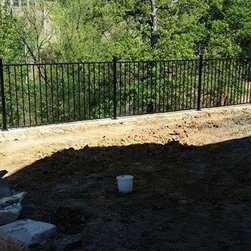 """Ornamental Iron Fence Addition - This client came to us with a problem. They had an existing wooden privacy fence that led into an existing iron fence that protected them from falling off of the 8 foot drop off at the rear of their back yard. They had removed the wooden fence and wished to have a matching iron fence built to tie into the existing iron fence. I assured the client that it would not be a problem. I matched the existing fence exactly to each detail. The 4 foot tall decorative iron fence was powder coated for a beautiful and long lasting finish. The 2"""" 14 gauge powder coated steel posts were anchored to the massive rock wall with heavy duty 3/8"""" steel wedge anchors. They also had a not so sturdy hand rail that went down the 13 feet of stairs that led to the grassy area below the back yard. The client has a toddler and I was concerned about him using the stairs with the hand rail in the condition that it was, so for good measure I added some 1 1/4"""" square tubing to match the existing at no charge. Doing so greatly strengthened the hand rail making the homeowner feel much safer about a descent into the lower grassy area."""