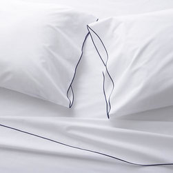 Belo Blue California King Sheet Set - Clean, basic white bedding upgrades in soft, smooth cotton percale, beautifully contrasted with a graceful blue overlocking stitch on the flat sheet and pillowcase. Generous fitted sheet pockets accommodate thicker mattresses. Sheet set includes one flat sheet, one fitted sheet and two pillowcases. Bed pillows also available.