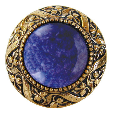 "Inviting Home - Victorian Knob (antique brass with blue sodalite) - Victorian Knob in antique brass with blue sodalite semi-precious stone 1-3/8"" diameter Product Specification: Made in the USA. Fine-art foundry hand-pours and hand finished hardware knobs and pulls using Old World methods. Lifetime guaranteed against flaws in craftsmanship. Exceptional clarity of details and depth of relief. All knobs and pulls are hand cast from solid fine pewter or solid bronze. The term antique refers to special methods of treating metal so there is contrast between relief and recessed areas. Knobs and Pulls are lacquered to protect the finish. Alternate finished are available. Blue Sodalite Semi-Precious stone. Blue Sodalite is a royal blue colored stone that usually has some white or gray-colored streaks. Blue Sodalite looks a bit more crystal-like. It was named by Professor Thomas Thompson who was called in to identify the specimen that was brought from Greenland to Denmark during the time of the Napoleonic wars - he identified it at first as Sodium Aluminum Silicate Chloride. The stone is associated with the Astrological sign Sagittarius and is thought to promote focus clearing mediation and calming of fears. Victorian Jewel pulls and knobs will allow you to have so much fun with the design. The pulls and knobs come in five different kinds of semi-precious stones: Black Onyx Tiger Eye Blue Sodalite Red Carnelian and Green Aventurine. You can even use all of the different colors of the semi-precious stones on one cabinet fa�ade�which would give it an eclectic and playful look."