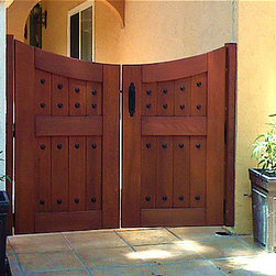 Hacienda Wood Gates - A double swing, reverse archtop gate with decorative clavos -  Hacienda style wood gate by Sederra