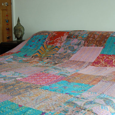 Dusky Pink Kantha Quilt - This gorgeous kantha bedspread/throw is made up of dusky pink, lilac and turquoise patchwork and is lined with a coordinating material. Patches of fabric have been sewn together and then the whole bedspread has been double stitched by hand in the kantha style to create it's unique texture and appearance. These striking bedcovers are all handcrafted which means each one is truly unique.