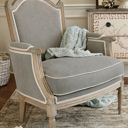 Andorra Armchair - Drawing inspiration from an antique our designers fell in love with on their travels through the tiny mountainous region of Andorra, this bergère chair replicates the original's embracing shape and gorgeous cathedral-style back. Richly upholstered in fine grey linen with a contrast welt (for a soupçon of Parisian chic), the upholstered back and down-wrapped seat cushion invite hours of refined relaxation. A wire-brushed finish and hand-rubbed taupe stain give the solid oak frame the aged appearance of an heirloom find.