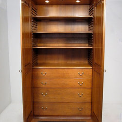 """The No. 570 Armoire Shown in Cherry, Sauterne, Standard - The No. 570 Armoire is a large, highly adaptable vertical cabinet that can be fitted out for whatever purposes you have in mind. In simple terms, you could make a giant chest of drawers or a flight of a dozen or so shelves, or some combination of the same. You could adapt the interiors to hold home entertainment equipment. As shown, this item comes with adjustable (2) 9"""" drawers, (2) 6"""" drawers, (4) shelves as well as two, three way lights. Customization including fold down desk, wet bar, touch lights, LED tape, LED lights, glass doors or shelves, custom sizes and configurations available."""