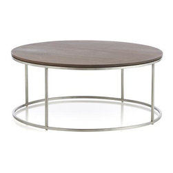 Frame Round Coffee Table - Streamlined stainless steel comes round to greet a tabletop of solid American walnut, contrasting and highlighting metal and wood to create a timeless, modern table. Round design and airy open frame works perfectly with other pieces, lending itself to all sizes of sofas and room d�cor. Table may exhibit graining, knots, splitting and mineral deposits, naturally occurring and prized attributes of pure wood.