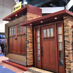 International Builders Show 2014 - Coordinated curb appeal: Clopay Reserve Collection custom wood carriage house style garage door and Clopay Craftsman Collection fiberglass front door. Show in complementing stain finish, with rectangular windows and optional decorative dentil shelf molding.