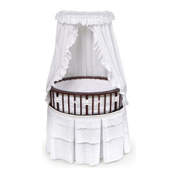 Badger Basket - Cherry Elite Oval Baby Bassinet - White Eyelet Bedding - Sure to be used for all the babies in the family! Our Elite Bassinet in White Eyelet Bedding offers a traditional oval shape with a very upscale furniture look! Interior measures 32 in. L x 25 in. W x 7.5 in. H. Bedding set includes a skirt, padded bumper, fitted sheet, canopy, and mattress. Also includes caster wheels and storage shelf beneath. The Elite Bassinet can be used for infants up to 20 lbs or until Baby can push up/roll over. Easy assembly with illustrated instructions. Extra sheets also available in White and Ecru.