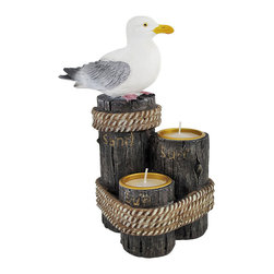 `Sea Breeze` Seagull on Pilings Double Tea Light Candle Holder - This lovely double tea light candle holder features a nautical theme of a seagull sitting on one of a trio of pilings. The other two pilings have recessed tops to hold tea candles perfectly. The pilings are marked with `Sun`, `Surf` and `Sand`, respectively. Measuring 7 1/2 inches tall, 6 inches wide, and 4 1/2 inches deep, it has excellent detail, from the grain of the wood on the pilings to the individual feathers on the seagull. It adds a great nautical accent to dressers, end tables and coffee tables, and makes a great gift.