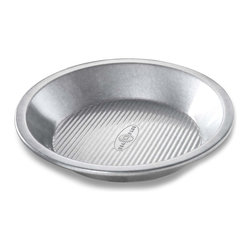 USA Pans 9 Inch Round Pan - The USA Pan 9 Inch Round Pie Pan has been designed with many of the same standard features of industrial baking pans. Each pan is constructed of aluminized steel the material of choice for commercial bakeries. Metal thicknesses have been selected that allow even heat distribution and maximum service life. Our pans also use steel wires in the rim construction of most pans to provide additional strength and resist warping. Each pan is coated with AMERICOAT© Plus a proprietary silicone coating that nearly all North American bakers prefer over dark non-stick coatings. AMERICOAT© Plus is a clear non-stick environmentally friendly coating that is specifically formulated for superior baking and does not contain any PTFE's or PFOA's.USA Pan bakeware features a corrugated or fluted design. The corrugation maximizes pan strength and prevents warping denting and other effects of everyday use. Corrugation also minimizes surface contact with baked goods which translates into an evenly baked product that is easily released. USA Pan has been developed by the world's largest manufacturer of industrial bakeware and has been providing the world's leading commercial bakeries with the highest quality baking pans for over 50 years. When you purchase a USA Pan you are buying products that meet industrial standards for innovation quality and durability. Put simply our pans are the best available and are proudly produced in the UNITED STATES OF AMERICA.