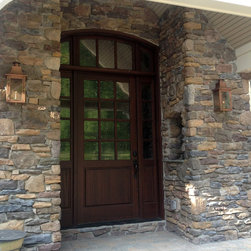 Custom Wood Doors - Custom arched entry door with sidelights and transom made from mahogany wood and stained dark chocolate sets off the entryway of this new home.  The door was hand crafted in Hershey, PA and shipped to the job site.