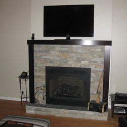 Fireplace Xtrordinair, Collinswood Designs, RealStone Systems - Direct Vent Gas Fireplace Projects - We tore out a small, ugly B-Vent gas fireplace and installed this larger direct vent gas fireplace which was a better fit for the room. This required running gas and electric to the unit as well as running the cables for the TV behind the wall. After raising the unit up and building out a hearth, we installed Sierra stone panels (accented by Blue Stone hearth tiles) and a very pretty cherry surround. The result was a modern look which really brightened the room.