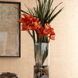 "Horchow - Red Orchid in Clear Vase - Enticing red orchids and spiky green foliage combine to refresh the room with a startling pop of color. Handcrafted of poly-silk cymbidium orchids and dried, preserved basil bulb foliage. Arranged in a clear glass vase with acrylic ""water"" and river...."