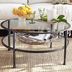 TANNER ROUND COFFEE TABLE - Our glass-topped coffee table keeps a room open and light. Its round shape works especially well with an L-shaped sectional, and its also a great fit in smaller spaces. Its top and shelf provide plenty of room for a variety of uses.