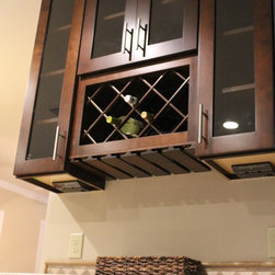 """Ritchson - Wellborn cabinetry  in Prairie door style. Maple wood specie and sienna glaze. 42"""" wall cabinets. Silver nickle hardware contrasting with dark cabinetry. Granite counter tops with a granite back splash."""
