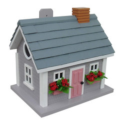 """Home Bazaar Inc. - Vineyard Cottage - Grey - This quaint, ocean gray cottage style birdhouse features two red flower window boxes with an inviting pink door. Grey shingles and a brick chimney top it off. Our Vineyard Cottage Birdhouse is constructed of exterior grade ply-board with poly-resin details.This style is a fully functional birdhouse with removable back walls, drainage, ventilation, mounting bracket and a 1 1/4"""" entry hole.The convenient, swing-up paddle-board attached to the back makes hanging this beautiful birdhouse as pleasant as walking along a Martha's Vineyard beach."""