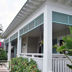 Custom-Made Louvered Shutters in a Pastel Green Finish  for an Outdoor Porch - Orange County, CA - This front door porch was beautifully finished with Bahama style shutters for protection from the sun while enjoying a sunny afternoon in the seating area.