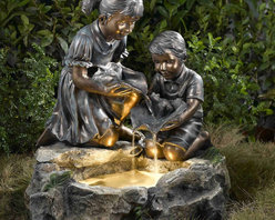 "Jeco - Fratelli Siblings Rock Outdoor/Indoor Fountain with Light - ""The detailed resin casting used to construct this fountain enables you to enjoy the texture of the children's hair and clothes. The figures feature a painted bronze finish that has been painted to create aged, weathered nuance. The children hold lily pads to create a water cascade with the boy also supporting an adorable frog. The Fratelli Fountain Includes a halogen bulb fixed into the bottom of the water reservoir for a magical nighttime effect. The base has a faux stone finish with green leaf accents. Patented bronze finish figures. Faux stone finish base with green leaf."