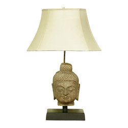 China Furniture and Arts - Stone Buddha Head Table Lamp with Shade - Delicately hand-carved in the likeness of Buddha, this lamp will bring peace wherever it is placed. A wooden base is specially made to complement this work of art and provide stability for placement on any surface. The ivory tone linen shade provides subtle yet adequate lighting. Requires one 75 watt max bulb (not included).
