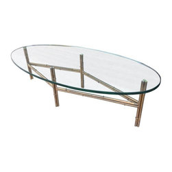 Pre-owned Metal Faux Bamboo Coffee Table - A totally fabulous vintage faux bamboo coffee table in a brass finish. Thick oval glass in wonderful condition. Minor scratches on the table surface, but no chips. Base shows some signs of wear with wonderful patina. Circa 1970s USA.
