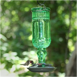 "Perky Pet 24 oz. Green Antique Bottle Hummingbird Feeder - What tunes will the birds be humming when they sip sweet nectar from the Perky Pet 24 oz. Green Antique Bottle Hummingbird Feeder? Perhaps """"Sugar ahh honey honey …"""" That's the kind of uplifting vibe you'll get from this sunny green antiqued glass feeder – it's as classic as the Archies song quoted above. With a capacity to hold up to 24 ounces of nectar there will be plenty of food to go around and with four flower feeding ports with brushed silver accents there's plenty of room for all. Cleaning is also simple with the removable base and hanging is a breeze with the attached metal hanger. About Woodstream Corp With more than 150 years of experience Woodstream Corp is privately-held company and a leading manufacturer of quality-branded products for pets and wildlife natural solutions for lawns and gardens wild bird feeding products and outdoor living decor. Woodstream's growth has been fueled by a consumer-driven approach to product development focusing on innovation quality safety and a commitment to an industry-leading level of service to retailers and consumers. For example a key focus for Woodstream Corp. has been to add organic and/or environmentally friendly products. It has taken a pro-active approach to preserve our environment and wild animals. About Birdfeeders.com Whether you're an experienced hobbyist or an amateur bird watcher there is a feeder to fit your style at Birdfeeders.com where you will find a substantial selection of quality bird feeding products at competitive prices. If you love watching birds in your backyard and want to attract more visit Birdfeeders.com for helpful bird watching and bird feeding advice. You can access the company's popular bird library for additional information about specific birds and then browse its collection of quality bird feeders feeder accessories bird baths and bird houses."