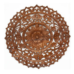 Kammika - Reclaimed-Teak Inlay Lotus Panel - Our Lotus Panel Reclaimed Recycled Teak Wood Inlay Round 60 centimeter (Approximately 24 inch) Diameter in Eco Friendly Natural Livos Light Teak Oil Finish is a detailed carving of our Lotus theme in a smaller round size. Several recycled rough-hewn Reclaimed Teak planks from old dwellings and community buildings are joined together and then carved with an intricate Lotus pattern as a single unit. The Lotus symbolizes purity in the Buddhist sense, and as such is a cherished theme. Use several of the same or other shapes to create a unique wall pattern or highlight a space. The panel has two embedded flush mount Keyhole hangers on the back. This elegant piece is carved out of reclaimed, recycled old Teak wood selected to match as close as possible in thickness and colorations. Variations in wood color are evident, although the carvers strive to make as close a match as possible before starting. Still the colors will vary naturally just like the trees from which the wood came many years before varied. Although they do not perfectly match in thickness, the design is carved in such a way as to match closely from panel to panel. Hand crafted from reclaimed recycled sustainable Teak wood, we make minimal use of electric hand sanders in the finishing process. All products are dried in solar and or propane kilns. No chemicals are used in the process, ever. After each eco friendly art piece is carved, kiln dried, sanded, and finished, they are packaged with cartons from recycled cardboard with no plastic or other fillers. As this is a natural product, the color and grain of your piece of Nature will be unique, and may include small checks or cracks that occur when the wood is dried. Sizes are approximate. Products could have visible marks from tools used, patches from small repairs, knot holes, natural inclusions or holes. There may be various separations or cracks on your piece when it arrives. There may be some slight variation in size, color, texture, and finish color.Only listed product included.