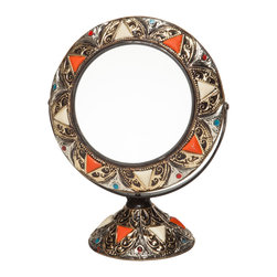 "Moroccan Vanity Mirror - This free-standing vanity mirror brings a touch of exotic Morocco to your bedroom or bath. The swivel frame and stand consist of hand-formed and embossed brass-colored metal and henna-dyed bone inlays. Note: base is hollow; total weight is approximately 19 ounces (lighter than it appears). Frame measures 8.5"" diameter, glass is 5.5"" diameter, overall height is 11""."