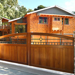 Craftsman Wooden Driveway Gate - Driveway gates can be built on a sloped driveway, as shown here.  A steel support frame is attached to the back side, which allows the gate to last for many years.