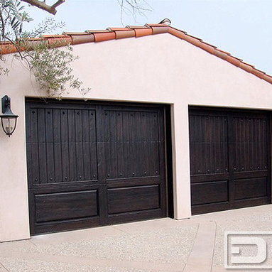 Dynamic Garage Door - California Dream 12 | Dark Wood (Espresso) Traditional Custom Garage Door Design - The rich, dark-espresso stain on these Custom Cedar Garage Doors is a bold feature that balances the rugged sand blasted wood used on these doors. Sand blasting wood brings out the heavy ridges of the natural grain that make solid wood such an excellent building subject on many of our doors. Dynamic Garage Door combines the ever-so- unique patterns found in natural wood and emphasizes such unique characteristics of wood to make a design statement when creating garage doors that make the architecture of any home bolder. Custom designing garage doors for different home styles is our specialty. Combining our knowledge in the garage door manufacturing industry we are able to produce some of the most gorgeous garage doors seen throughout the country. We can install design, craft and install your garage doors in the state of California or design, craft and ship to any other state in the U.S.