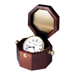 "Howard Miller - Howard Miller - Oceana Table Top Clock - Whether you make your home on land or at sea, this beautiful captain's clock will make a fashionable impression on your friends and special guests alike. It's set in an octagonal, felt-lined case, and turns freely on a gold-finished metal rod. The box itself is finished in a Windsor cherry color for an attractive look. * A polished brass gimbaled captain's clock is housed in a felt lined octagonal chest. . A push button catch will open the lid to reveal the white dial with black Roman numerals and hands with a brass second hand. . A felt bottom protects your desk or tabletop. . An octagon plate for engraving is included (unattached). . Finished in Windsor Cherry on select hardwoods and veneers. . Quartz movement includes battery. . H. 3-1/2"" (8 cm). W. 6-1/2"" (17 cm). D. 5"" (13 cm)"