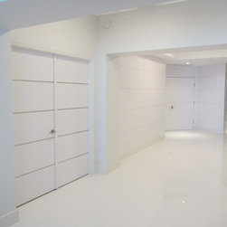 modern invisible doors and wall paneling - white invisible doors with stainless steel strips and wall paneling.
