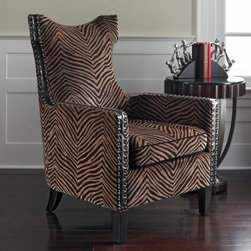 Kimoni Wingback Chair - Wildly stylish the Kimoni Wingback Chair is like no other you've seen before. A hardwood frame gives this chair durability and strength while the black-and-tan zebra-print upholstery gives it a unique and contemporary twist. Black piping lines the outer edges of cushions and other corners. The outer frame is covered in chocolate-colored leather that's trimmed with nail heads on both sides. This blend of materials and textures further enhances this chair's distinct style. Ebony-finished legs are curved in the back and will need to be attached to the chair bottom. The removable seat cushion makes cleaning easier.About Uttermost ProductsThe mission of the Uttermost Company is simple: to make great home accessories at a reasonable price. This has been the objective since the family-owned business was founded over 30 years ago. Uttermost manufactures mirrors art metal wall art lamps accessories clocks and lighting fixtures in its Rocky Mount Va. factories. Uttermost provides quality furnishings throughout North and South America Europe and Asia from its state-of-the-art distribution center located on the West Coast of the United States.