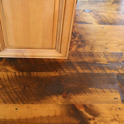 Hull Forest Products - Circular Sawn Wide Plank Pine Wood Floors - Eastern White Pine flooring mill-direct from Hull Forest Products. Photo shows circle sawn solid wide pine plank floor with Walnut Old Masters stain and Waterlox satin tung oil finish. Floor planks shown are 7-11 inches wide.  (Widths from 5-23 inches are available.) This is newly sawn premium grade Eastern White Pine that has been skip planed and given circular saw marks for an antique look. The floor also features reproduction nails. Our wide pine is carefully selected from logs predominantly twelve feet and longer in order to ensure even growth and live red knots.  These logs come from second and third growth pine trees grown in historic and protected Connecticut forests, and the logs are harvested during the cold winter months for the best color retention.  Only sound red knots and very occasional small sound black knots or inclusions are allowed in this grade.