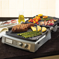 """Frontgate - Cuisinart Griddler Deluxe - Reversible and interchangeable plates function as contact grill, panini press, full griddle, full grill, half grill/half griddle, and top melt. Dual-zone temperature controls heat one or both plates from warm to 450°F. Extra-large grilling surface is ideal for entertaining large groups. Integrated drip tray collects grease and is easy to store. Cooking plates, drip tray, and scraping tool are dishwasher safe. From pancakes and panini to steaks and salmon, the Griddler Deluxe from Cuisinart combines six cooking options to help you prepare a great meal in minutes. It includes the new SearBlast feature that locks in the flavor of meats and fish. Plus, the extra-large surface expedites cooking family meals.  . Dual-zone temperature controls heat one or both plates from warm to 450 degreesF .  .  .  . Hinged top has six preset widths . Can sear foods at 500 degreesF for up to two minutes at a time . Brushed stainless steel housing . 1,800 watts of power . Limited 3 year warranty . 36"""" cord; 120V ."""
