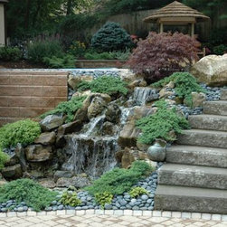 Upgrading Your Existing Backyard Retreat (Long Island/NY): - Where once stood an outdated moss rock waterfall, now stands a sophisticated and elegant fountain style water feature with three spilling sheets of water.
