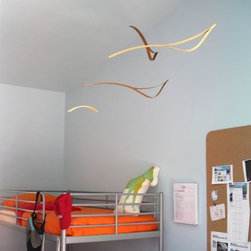 Schmitt Design - Rift Mobile by Schmitt Design - The configuration of the Schmitt Design Rift Mobile evokes three birds flying over a branch. Airy and dynamic, this mobile also highlights the beauty of the veneer used to make it. The bird-shaped forms show the two layers of bamboo veneer split apart and held in tension (hence, the Rift). The bamboo's beauty is further enhanced by a dual natural and amber finish combination. In 2012, Schmitt Design became the new name for Adrift Mobiles, founded by Brian Schmitt. The name change came about as, while still specializing in contemporary mobiles for adults, the company has expanded to include a line of award-winning modern lighting, clocks and furniture. All Schmitt Design pieces are created and manufactured in Sacramento, California.