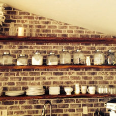 The beautiful craftsmanship of the floating reclaimed oak shelves and the brick