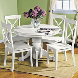 Magnolia White Dining Room Collection - In The Round. Our Magnolia White collection has an intimate and cozy feel, making it the perfect place to warm up with coffee in the morning or gather the family at dinner time. Its casual yet sophisticated approach to dining is evident in the stylish chairs with an X-back design and white finish. The classic pedestal table has a turned and faceted center support with shapely, contoured legs. A slanted edge on the tabletop adds a hint of contemporary appeal. Five piece package includes table and four side chairs, as shown.